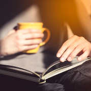 Hands holding a book and a cup of coffee.